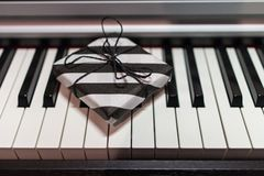 Подарочная коробка в striped черно-белой упаковке на клавиатуре рояля стоковое изображение