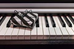 Подарочная коробка в striped черно-белой упаковке на клавиатуре рояля стоковые фото