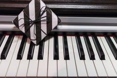 Подарочная коробка в striped черно-белой упаковке на клавиатуре рояля стоковое фото rf
