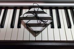 Подарочная коробка в striped черно-белой упаковке на клавиатуре рояля стоковые изображения rf
