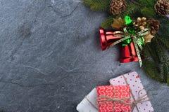 подарочная коробка ели колокола рождества с счастливого рождествами текста на камне Стоковое Изображение