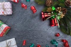 подарочная коробка ели колокола рождества с счастливого рождествами текста на камне Стоковая Фотография RF