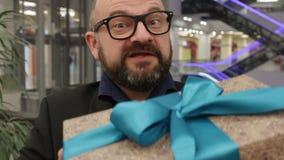 Подарочная коробка настоящего момента улыбки бизнесмена в руке конец вверх сток-видео