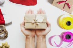 Подарочная коробка пакета удерживания руки, подарок на рождество подготовки на Рождество на белой таблице Стоковое фото RF