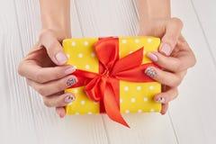 Подарочная коробка поставленная точки желтым цветом в женских руках Стоковая Фотография RF