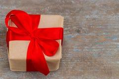 Подарочная коробка присутствующая при красная лента смычка и коричневые krafts оборачивая p Стоковая Фотография RF