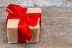 Подарочная коробка присутствующая при красная лента смычка и коричневые krafts оборачивая p Стоковые Изображения RF