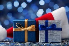 Подарочная коробка рождества 2 или настоящий момент и шляпа santa против голубой предпосылки bokeh Волшебная поздравительная откр Стоковое фото RF