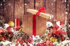 Подарочная коробка рождества представленная в середине украшений рождества на деревянных планках стоковые фото