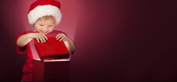 Подарочная коробка рождества счастливого мальчика открытая стоковое изображение