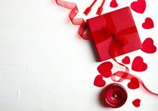Подарочная коробка с красной лентой, много декоративных красных сердец и свечой Стоковая Фотография RF