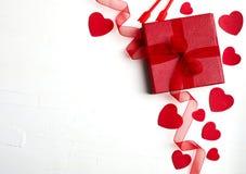 Подарочная коробка с красной лентой, много декоративных красных сердец и свечой Стоковое Изображение