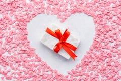 Подарочная коробка с красной лентой окруженной с сердцем сформировала рамку стоковое изображение rf