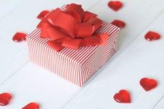 Подарочная коробка с красным смычком и сердца на светлой предпосылке стоковое фото