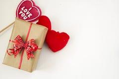 Подарочная коробка с красным смычком, красными пушистыми сердцами и сердцем сформировала леденец на палочке стоковое изображение