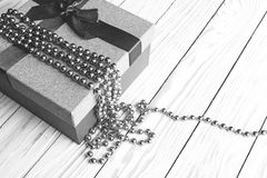 Подарочная коробка с лентой и шарики на деревянной предпосылке, черно-белом изображении крупного плана Стоковые Изображения