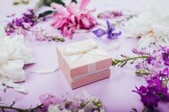 Подарочная коробка с свежими цветками на фиолетовой предпосылке праздник присутствующий Стоковое фото RF
