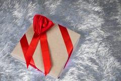 Подарочная коробка упакованная в бумаге и связанная с красной лентой с смычком в форме розы лежит на мехе фальшивки подушки Стоковая Фотография RF