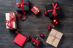 Подарочная коробка черных, красного цвета и ремесла рождества с красной лентой Стоковое фото RF