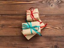 3 подарочной коробки бумаги Kraft с лентами на коричневом деревянном b Стоковые Изображения RF