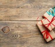 3 подарочной коробки бумаги Kraft с лентами на коричневом деревянном b Стоковое фото RF
