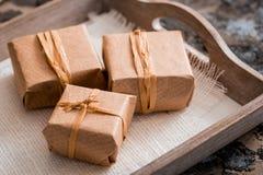 3 подарочной коробки в оболочке kraft на серой конкретной предпосылке на деревянном столе место для вашей надписи Стоковые Фото
