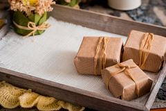 3 подарочной коробки в оболочке kraft на серой конкретной предпосылке на деревянном столе место для вашей надписи Стоковое Фото
