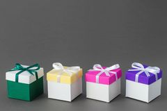 4 подарочной коробки с лентами на серой предпосылке Скопируйте космос для Стоковая Фотография