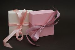 2 подарочной коробки с розовым смычком на предпосылке Брайна Подарок, день рождения сбывание стеклянной руки принципиальной схемы Стоковые Фото