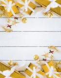 Подарочные коробки золота и блестящее рождество украшая детали на белых деревянных предпосылке панели, детале украшения и космосе стоковая фотография rf