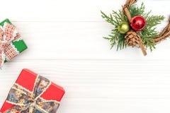 Подарочные коробки и венок ветви и конуса сосны на белой деревянной предпосылке Стоковое Изображение RF