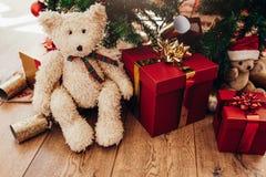 Подарочные коробки и мягкие игрушки помещенные около рождественской елки Стоковые Изображения RF