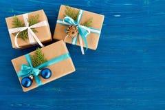 Подарочные коробки обернутые бумаги ремесла, лент и украшенных ветвей ели, голубых шариков рождества и конуса сосны на голубой пр Стоковая Фотография RF