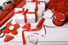 Подарочные коробки обернутые в лентах белой бумаги и красного цвета, сердцах, свечах, и рабочей поверхности для праздничной упако Стоковые Фотографии RF