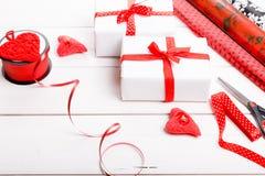 Подарочные коробки обернутые в лентах белой бумаги и красного цвета, сердцах, свечах, и рабочей поверхности для праздничной упако Стоковое Изображение RF
