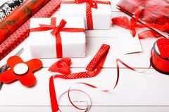 Подарочные коробки обернутые в лентах белой бумаги и красного цвета, сердцах, свечах, и рабочей поверхности для праздничной упако Стоковые Изображения