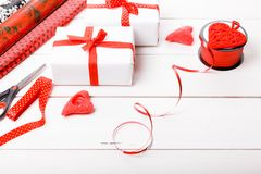 Подарочные коробки обернутые в лентах белой бумаги и красного цвета, сердцах, свечах, и рабочей поверхности для праздничной упако Стоковая Фотография