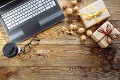 Подарочные коробки рождества, компьтер-книжка и кофейная чашка на деревянной предпосылке Взгляд сверху с космосом экземпляра для  Стоковая Фотография
