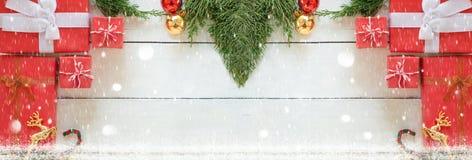 Подарочные коробки рождества красные с зелеными орнаментами сосны и украшать на белой деревянной предпосылке панели, плоско кладу стоковая фотография