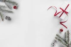 Подарочные коробки рождества на белой предпосылке с ветвями ели, конусами сосны, красным украшением стоковые изображения rf