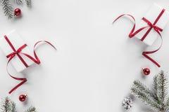 Подарочные коробки рождества на белой предпосылке с ветвями ели, конусами сосны, красным украшением Xmas и счастливая тема Нового стоковая фотография