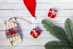 Подарочные коробки рождества, сани Санта и ветви ели на деревянной предпосылке, взгляде сверху стоковые фотографии rf