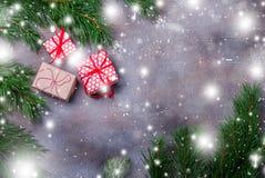 Подарочные коробки рождества с красной лентой на темной предпосылке с елью разветвляют Xmas и счастливый состав Нового Года Плоск стоковое фото