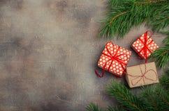 Подарочные коробки рождества с красной лентой на темной предпосылке с елью разветвляют Xmas и счастливый состав Нового Года Плоск стоковые фотографии rf