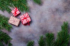 Подарочные коробки рождества с красной лентой на темной предпосылке с елью разветвляют Xmas и счастливый состав Нового Года Плоск стоковая фотография rf