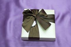Подарочные коробки с большим красным смычком против bokeh предпосылки мерцания party света Роскошный подарок Нового Года Подарок  Стоковые Фотографии RF