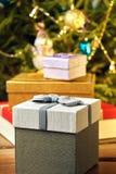 Подарочные коробки с смычками на крышках под рождественской елкой в кануне Нового Годаа Стоковое Фото