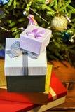 Подарочные коробки с смычками на крышках под рождественской елкой в кануне Нового Годаа Стоковая Фотография RF