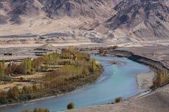 Подача реки через обрабатываемые земли с предпосылкой гор Стоковая Фотография