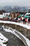 Подачи потока горы среди старых арендуемых домов и современная архитектура в сезоне в зиме, Zakopane highe стоковые фотографии rf
